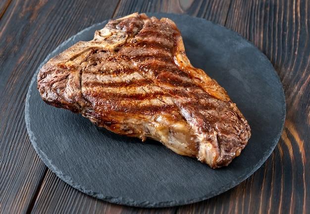 Жареный стейк на косточке на каменной доске