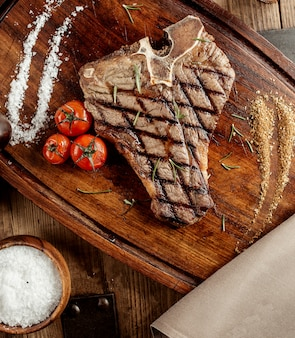 Grilled t-bone steak served with salt herbs and grilled cherry tomatoes
