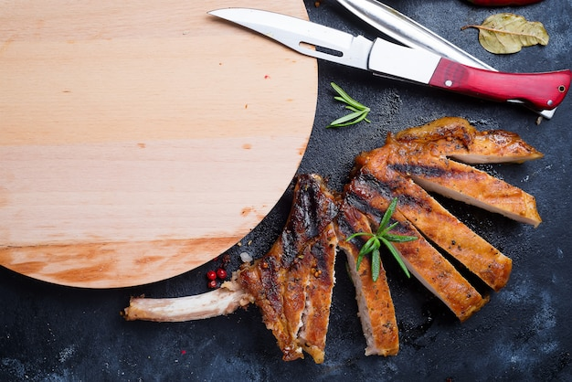 Grilled t-bone steak on stone table with wooden board. top view with copy space
