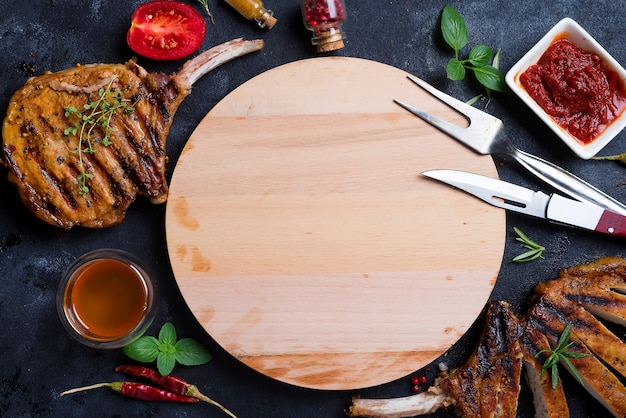 Grilled t-bone steak on stone table with wooden board.