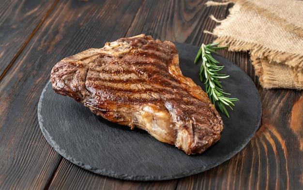 Жареный стейк на косточке со свежим розмарином на каменной доске