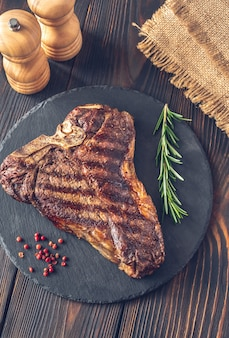 Grilled t-bone steak with fresh rosemary and red pepper on the stone board