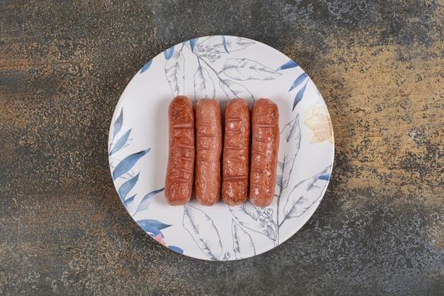 Gustose salsicce alla griglia sul piatto colorato.