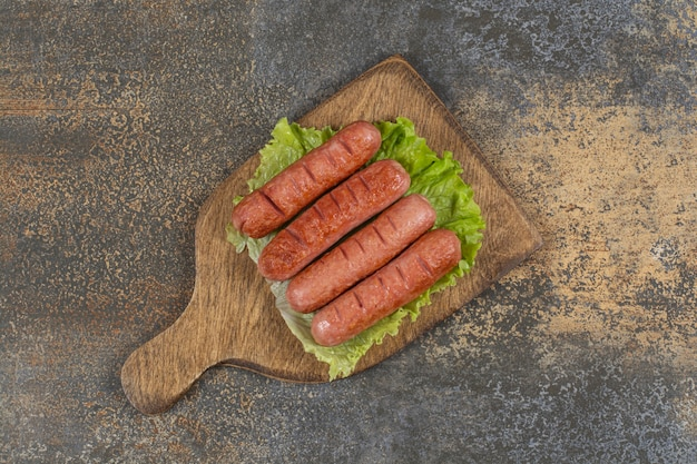 Вкусные сосиски на гриле на деревянной доске.
