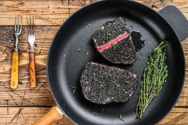 照り焼きマグロのステーキをフライパンで焼きました。木製の背景。上面図。