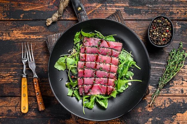 Салат из стейка из тунца терияки на гриле с рукколой и шпинатом.