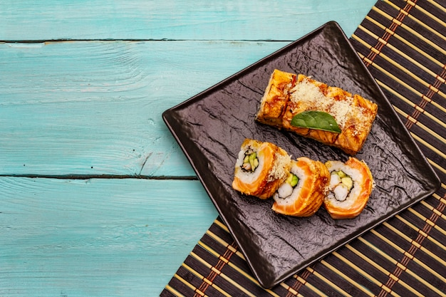 Grilled tiger prawn sushi. japanese or korean roll with different fresh ingredients. trendy turquoise background