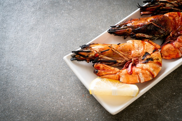 Жареные тигровые креветки или креветки с лимоном на тарелке
