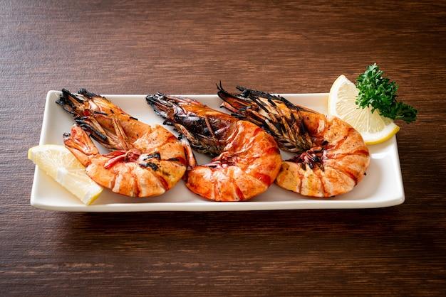 Жареные тигровые креветки с лимоном на тарелке
