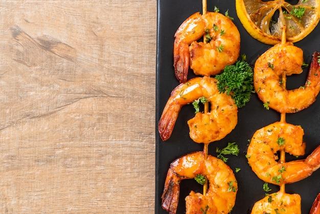 Grilled tiger shrimps skewers with lemon. copyspace
