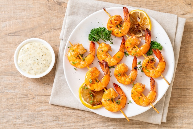 Grilled tiger shrimps skewers with lemon