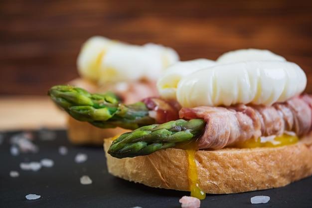 Жареный тост со спаржей в беконе и яйцом-пашот на деревянном
