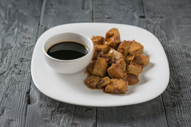 Жареный сыр тофу и соевый соус на белой тарелке. соевый сыр. вегетарианский продукт. плоская планировка.