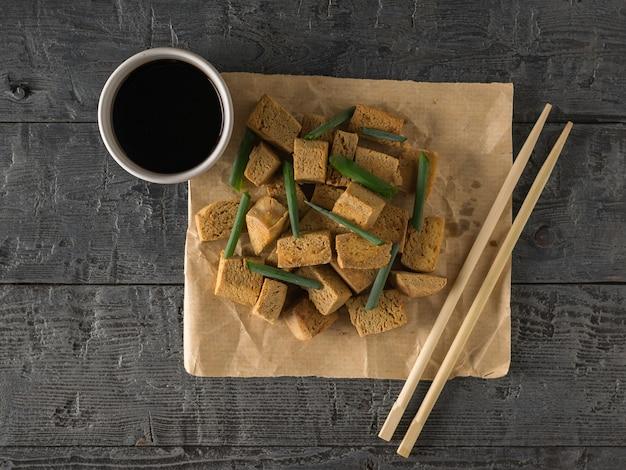 Жареный сыр тофу на бумаге и соевый соус на деревянном столе. закуска с сыром на гриле.