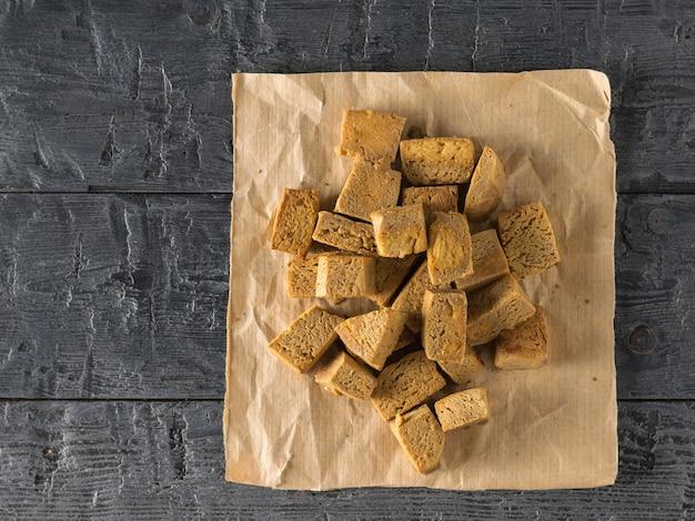 Жареный сыр тофу на бумаге на деревянном столе. закуска с сыром на гриле. плоская планировка.