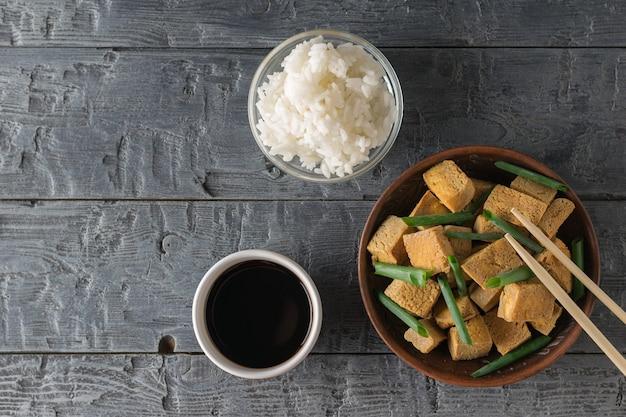 Жареный сыр тофу с зеленым луком, рисом и соевым соусом на деревянном столе. закуска с сыром на гриле. плоская планировка.