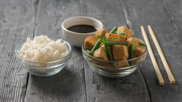 Жареный сыр тофу с зеленым луком, рисом и соевым соусом на деревянном столе. закуска с сыром на гриле.