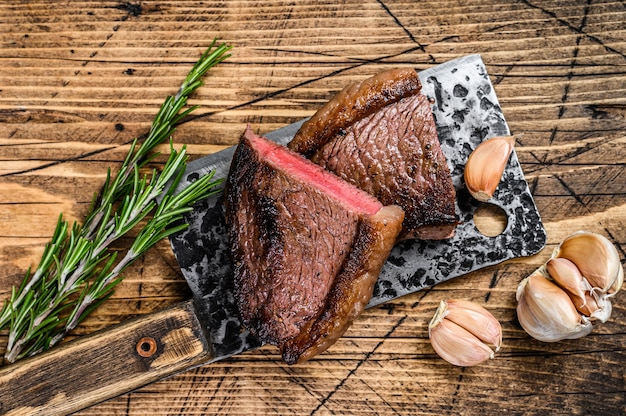 Жареный на гриле стейк из говяжьего мяса на тесаке на деревянном столе. вид сверху.