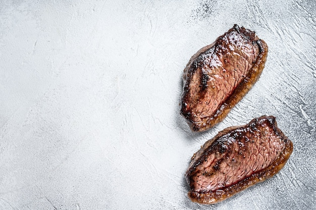 Grilled top sirloin cap or picanha steak. white background. top view. copy space.