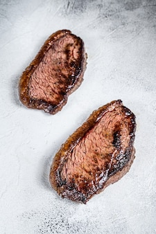 Grilled top sirloin cap or picanha steak. white background. top view.