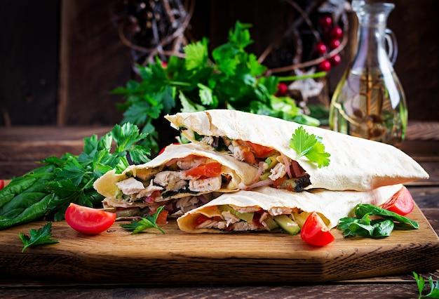 Роллы из тортильи на гриле с курицей и свежими овощами на деревянной доске. куриный буррито. мексиканская еда. концепция здорового питания. мексиканская кухня
