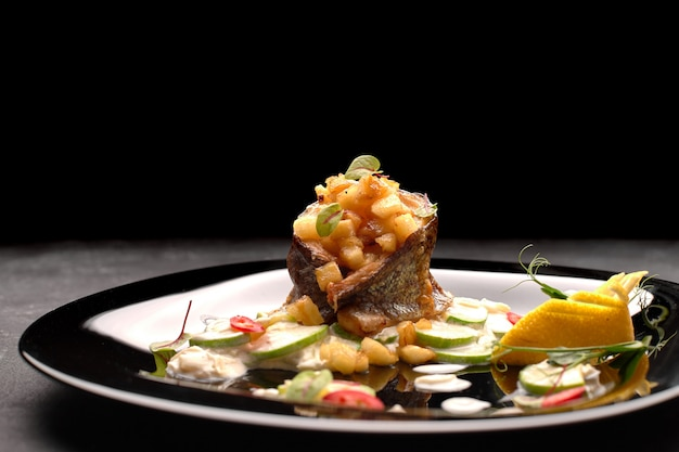 黒の背景に、野菜とマスのグリルフィレ