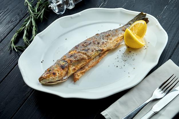 레몬과 함께 흰 접시에 숯불에 구운 송어
