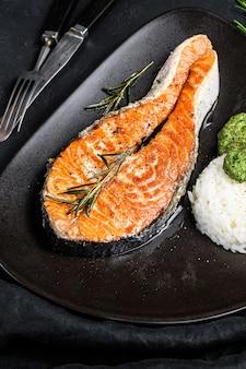 Стейк из форели на гриле с рисом и шпинатом. здоровые морепродукты. черный фон. вид сверху