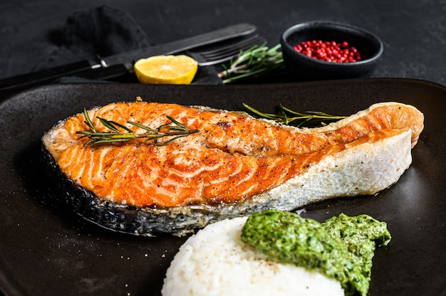 Grilled trout steak garnished with rice and spinach. healthy seafood. black background. top view