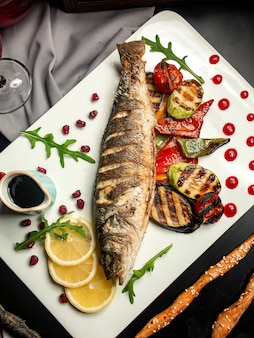 Grilled trout with eggplant zucchini bell pepper and pomegranate sauce