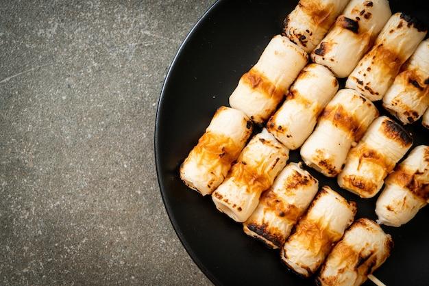구운 튜브 모양의 어묵 케이크 또는 튜브 오징어 꼬치 접시에
