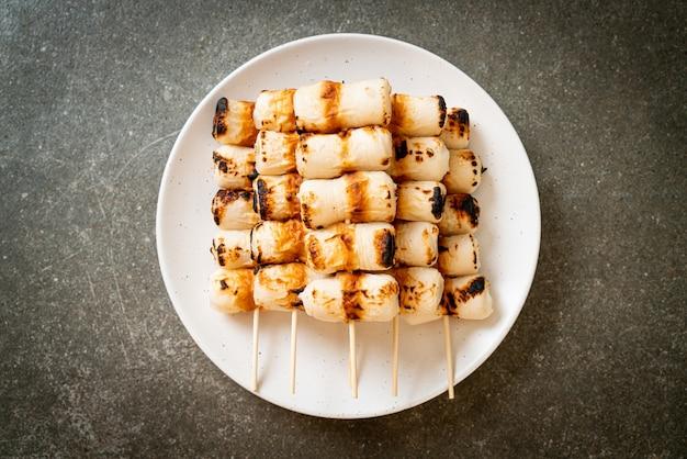 접시에 구운 튜브 모양의 생선 페이스트 케이크 또는 튜브 오징어 꼬치