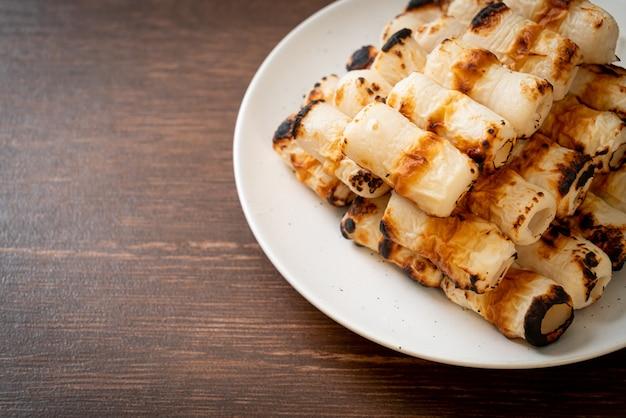 焼き魚のペーストケーキまたはプレート上のチューブイカの串焼き