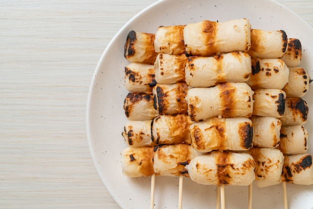 Grilled tube shaped fish paste cake or tube squid skewer on plate