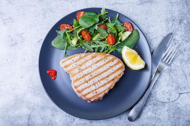 Стейк из тунца на гриле со свежими овощами, рукколой, шпинатом и лимоном. крупный план, вид сверху.