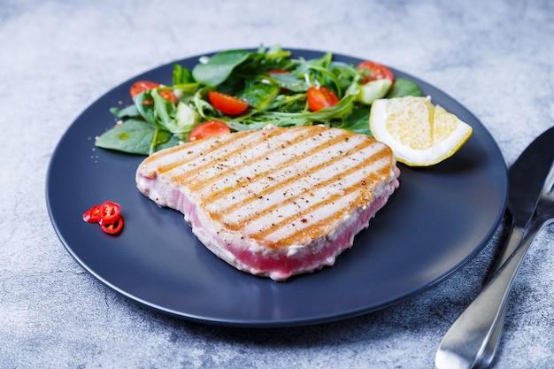 Стейк из тунца на гриле со свежими овощами, рукколой, шпинатом и лимоном. крупный план.