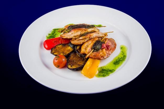 구운 칠면조 가슴살은 구운 야채와 페스토 소스를 곁들인 꼬치에 허브로 채워져 있습니다. 파란색 배경에 흰색 접시에 평면 위치 최고보기.