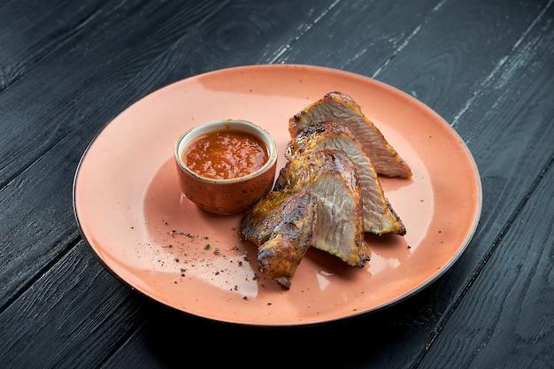 ターキーフィレの炭火焼き、ダークウッドの背景のプレートに赤いソースを添えて。七面鳥のケバブ
