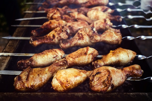 Голень индейки на гриле во время приготовления. курица, запеченная на вертеле на открытом воздухе. крупным планом вид.