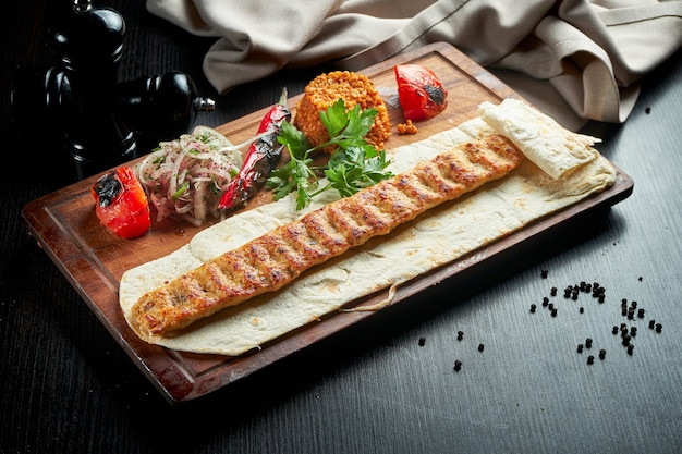 구운 야채, 양파, 쌀 나무 보드에 구운 터키 치킨 룰라 케밥. 어두운 테이블.