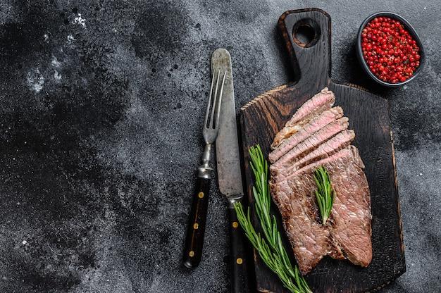 Стейк отбивной из мяса телятины на разделочной доске.