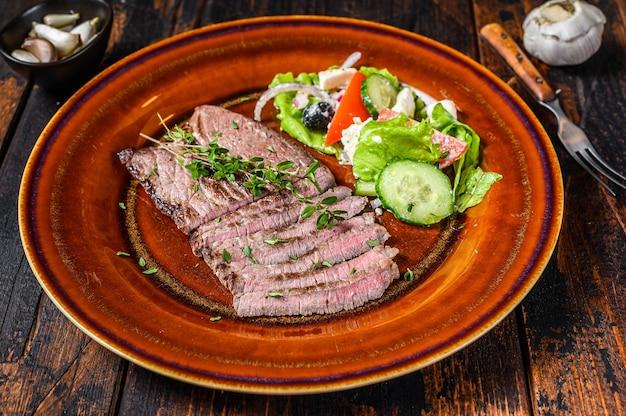 Стейк из телятины на гриле на тарелке с салатом.