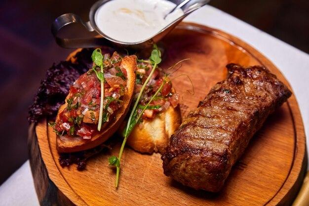 Стейк из телятины на гриле с томатной сальсой на деревянной тарелке. крупный план, выборочный фокус