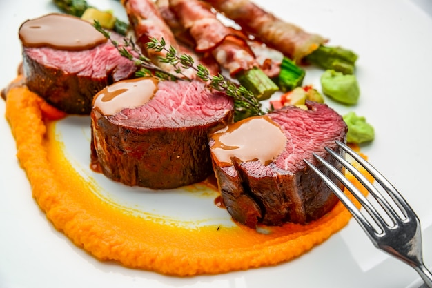 子牛のテンダーロインのグリル、サラダ、アスパラガスとベーコン添え。木製のテーブルの上
