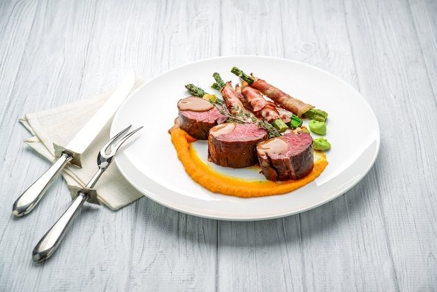 Grilled veal tenderloin with salad, with asparagus and bacon. on the wooden table