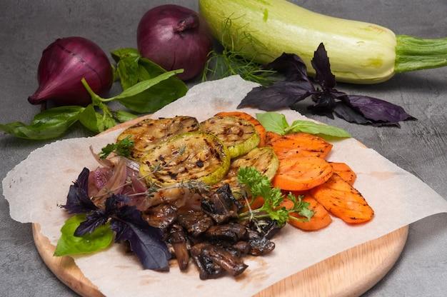 Жареные овощи и грибы на деревянной доске на сером фоне