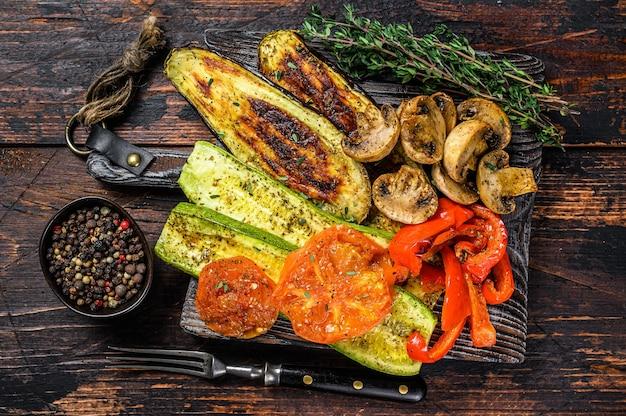 Жареные овощи болгарский перец, цукини, баклажаны и помидоры с сухими травами на деревянной доске. темный деревянный фон. вид сверху.