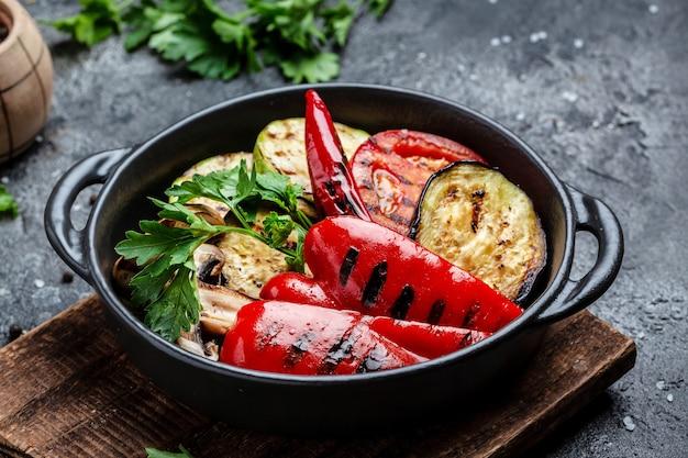 Овощи гриль красочный болгарский перец, кабачки, баклажаны с зеленью в чугунной сковороде-гриль