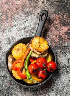 Жареные овощи на сковороде. на деревенском столе.