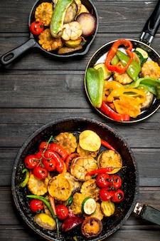 Жареные овощи в сковороде на деревянном столе.